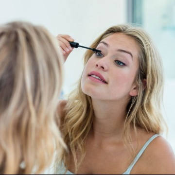 Smiling single mom putting on mascara in the bathroom mirror at home—ESME.com