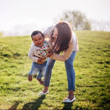 A happy interracial family, a white single mom and her African American son having fun in the park—ESME.com