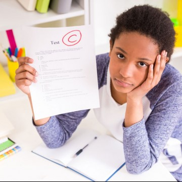 Unhappy schoolgirl sitting at the table and showing bad test results on colorful background, symbolizing that it's OK to let your kids make mistakes—ESME.com
