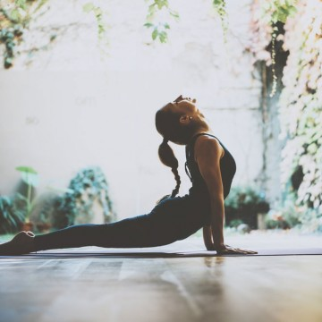 Young Solo Mom practicing yoga indoors—ESME.com