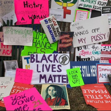 Protest signs are placed on a fence after the Women's March on Washington—ESME.com
