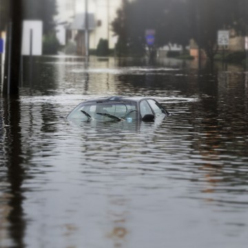 A flooded car in deep water, symbolizing how Solo Moms can prepare for a natural disaster—ESME.com