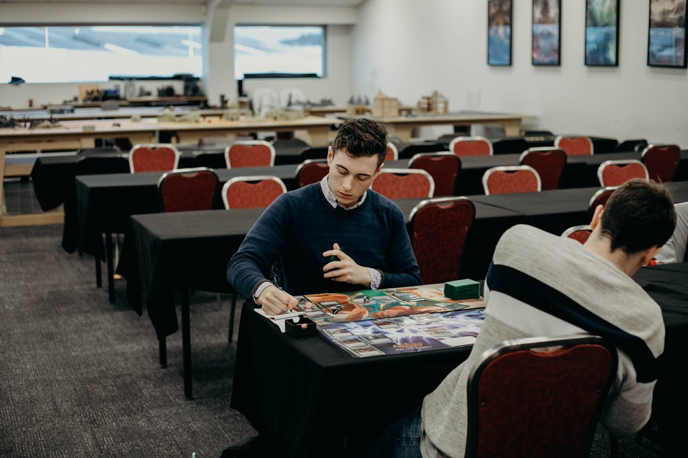 Jacob Pearson sits across from another player, in the middle of a game at a Road to Nationals Event