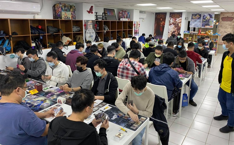A wide shot of the Cat Footprints Zhongli store during the Skirmish event, with lines of players sitting at tables, playing games of Flesh and Blood