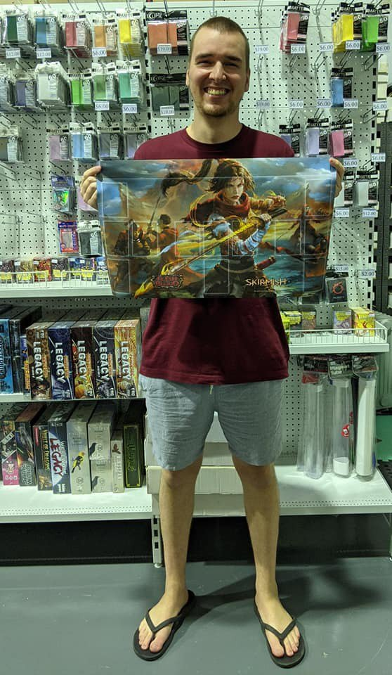Luke Fletcher, winner of the Top Deck Games Skirmish event, holding his prize playmat