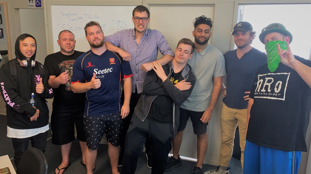 A photo of Shadowrealm Whangarei's Top 8 Players for their Skirmish event, making thumbs up or peace signs for the camera