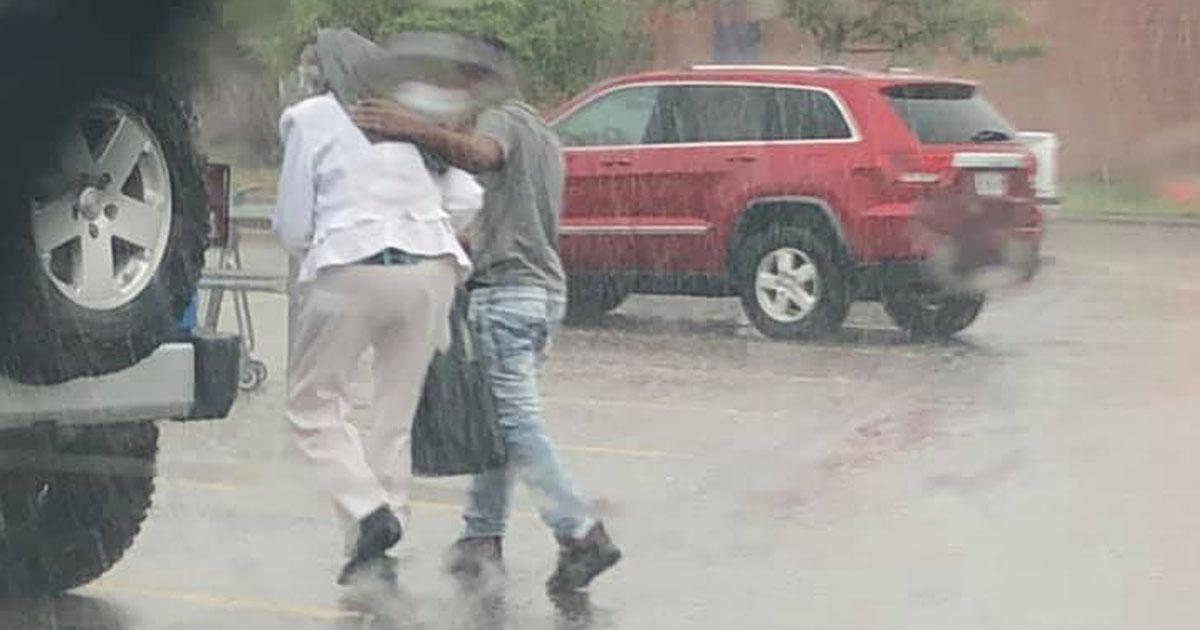 stranger-walk-elderly-woman-car-during-rain