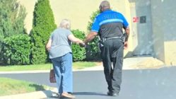 officer-helps-elderly-woman-walk