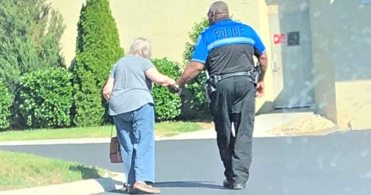 officer-helps-elderly-woman-walk