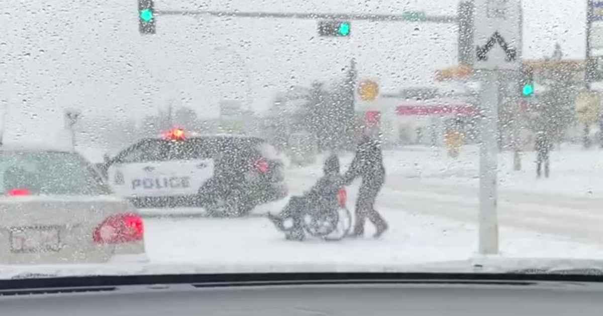 officer-helps-man-in-wheelchair-cross-street