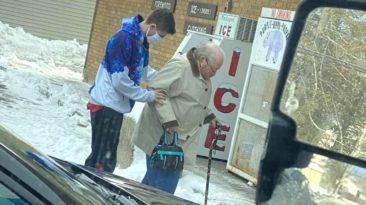 man-helps-elderly-woman-walk-across-ice