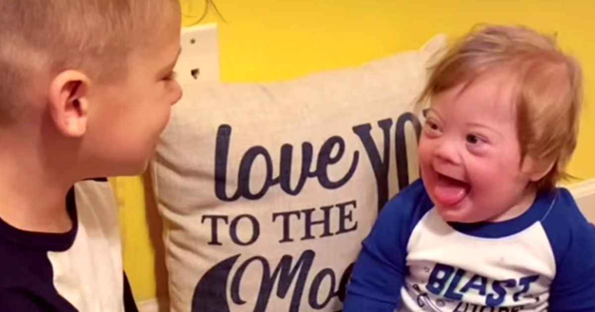 boy-singing-to-baby-brother-with-down-syndrome
