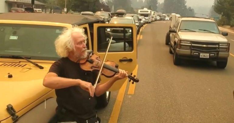 man plays violin in traffic Caldor Fire
