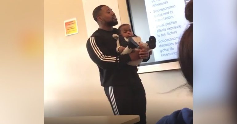 professor holds students baby