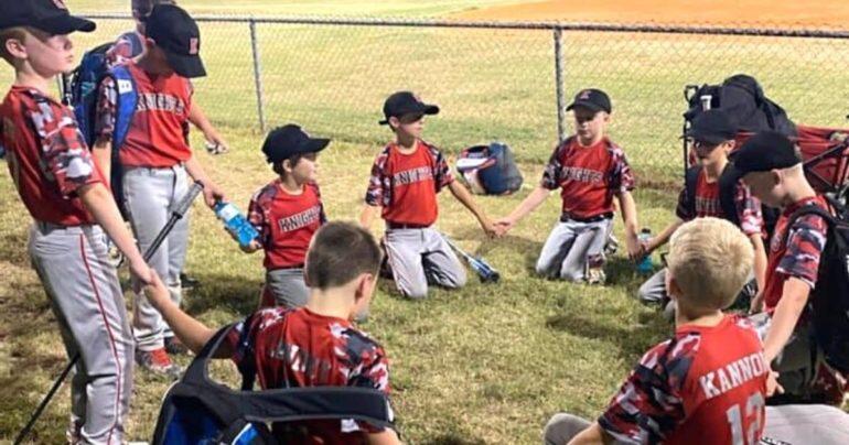 boys praying at ball field blake bastin