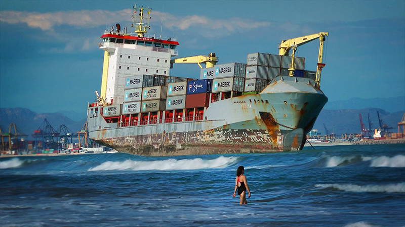 Freightened swimmers share the beach with a rusty container ship