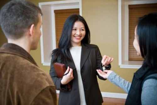 Realtor handling house key to new happy home owner