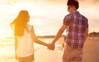 young couple enjoying a beach walk at sunset
