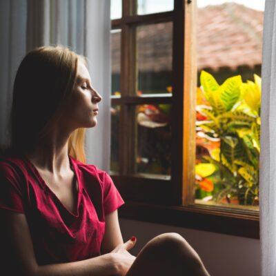 Vrouw thuis voor raam