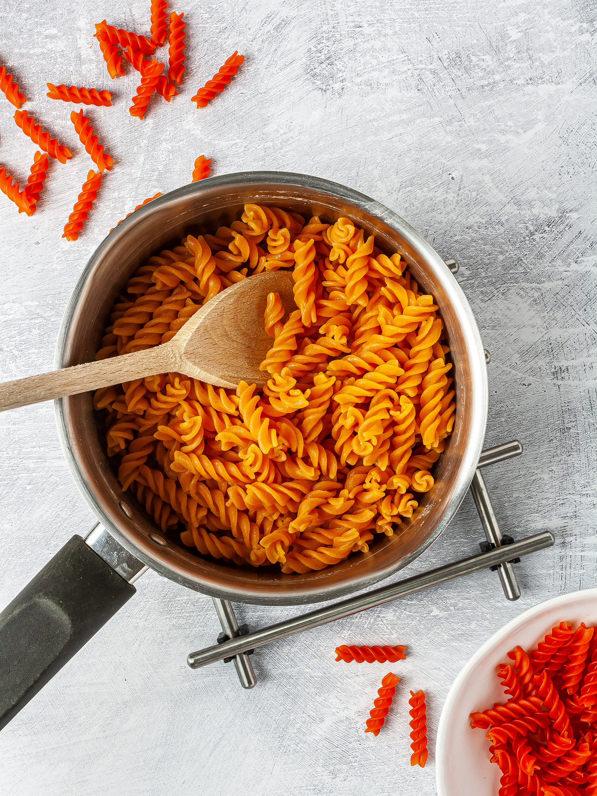 Dry and cooked red lentil pasta in a pot