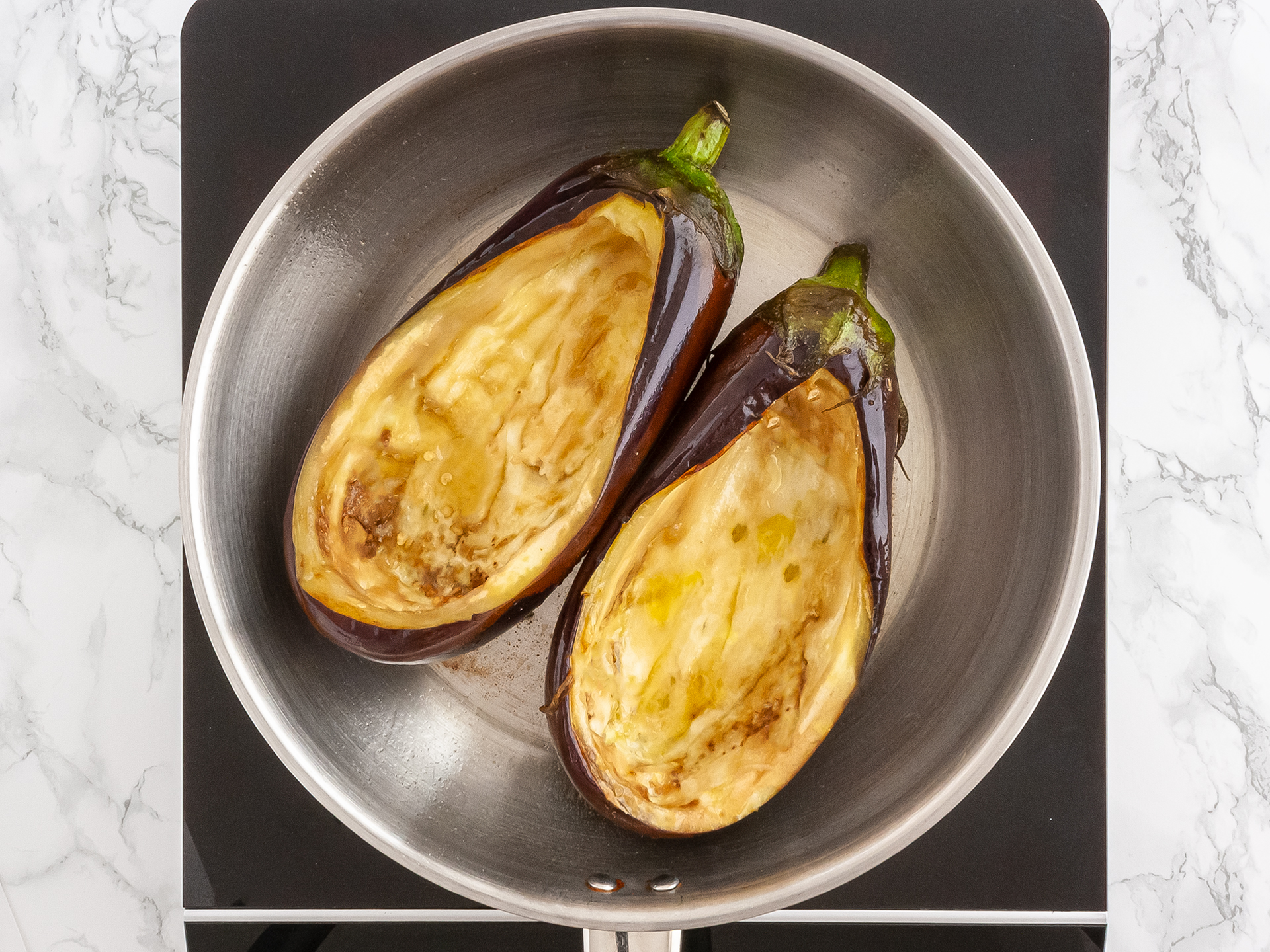 Two aubergines sliced and carved cooking in  a pan