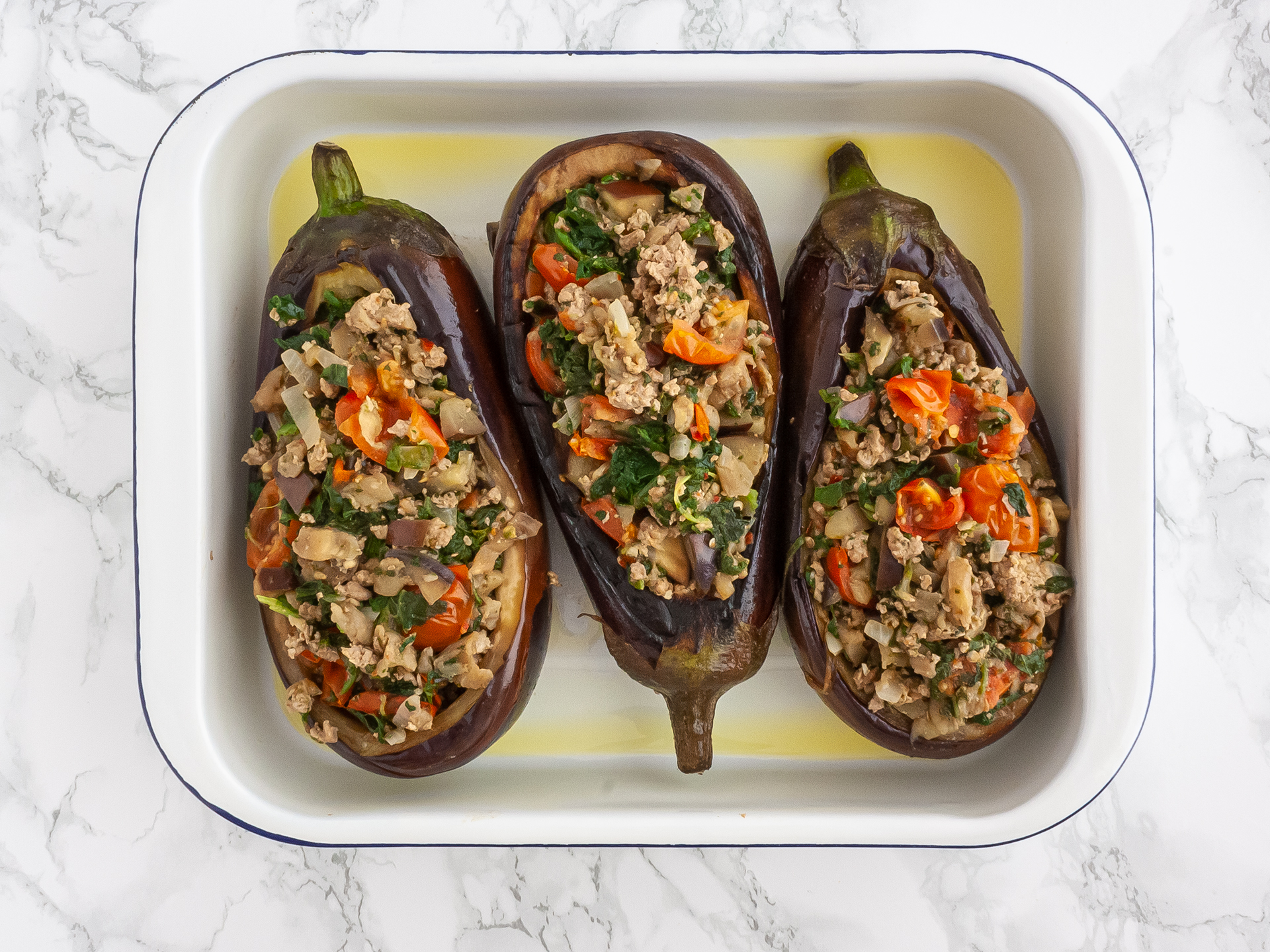 Aubergines stuffed with ketogenic filling into a roasting tin