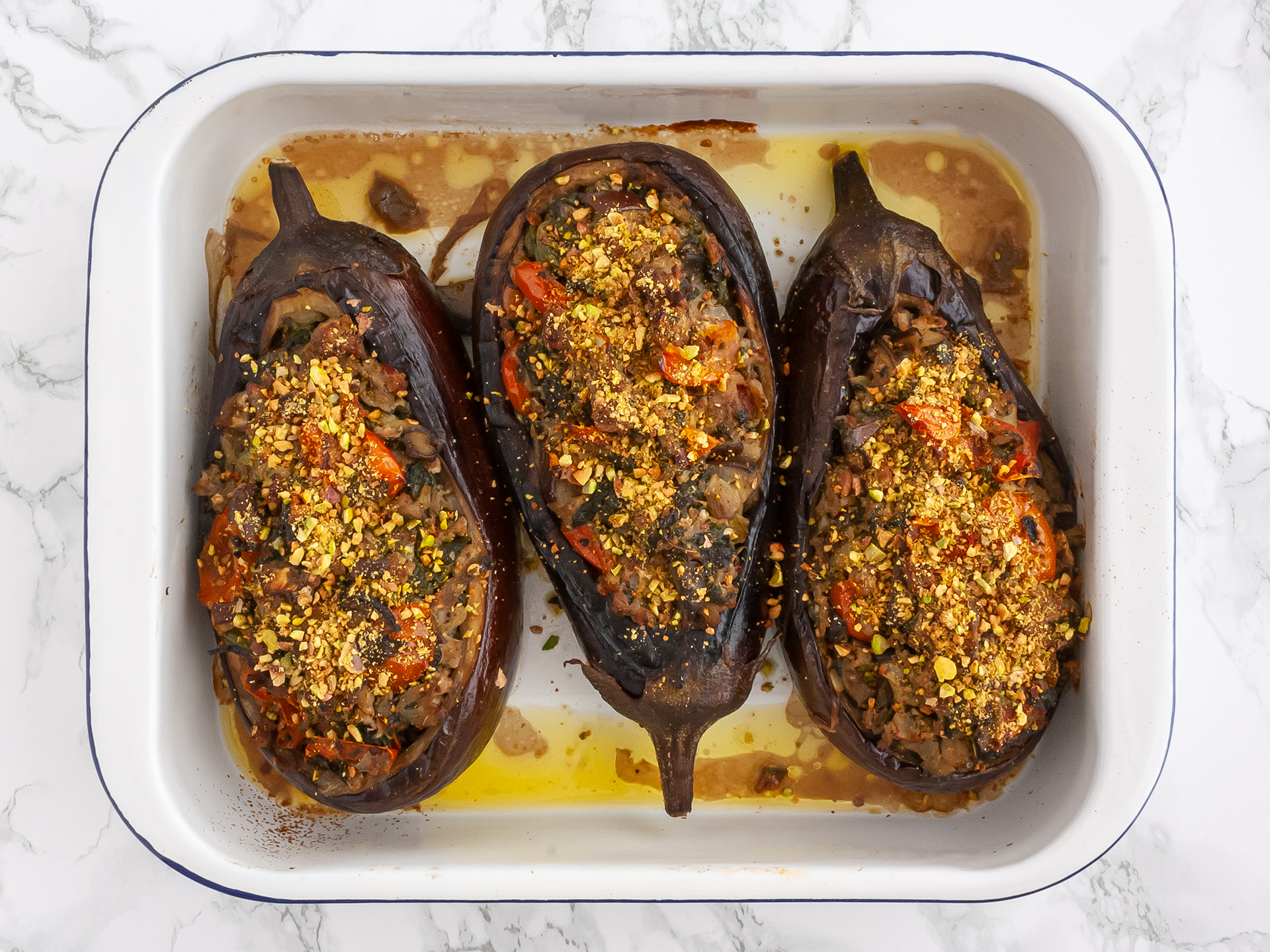 Cooked keto aubergines in a roasting tin sprinkled with roasted pistachios
