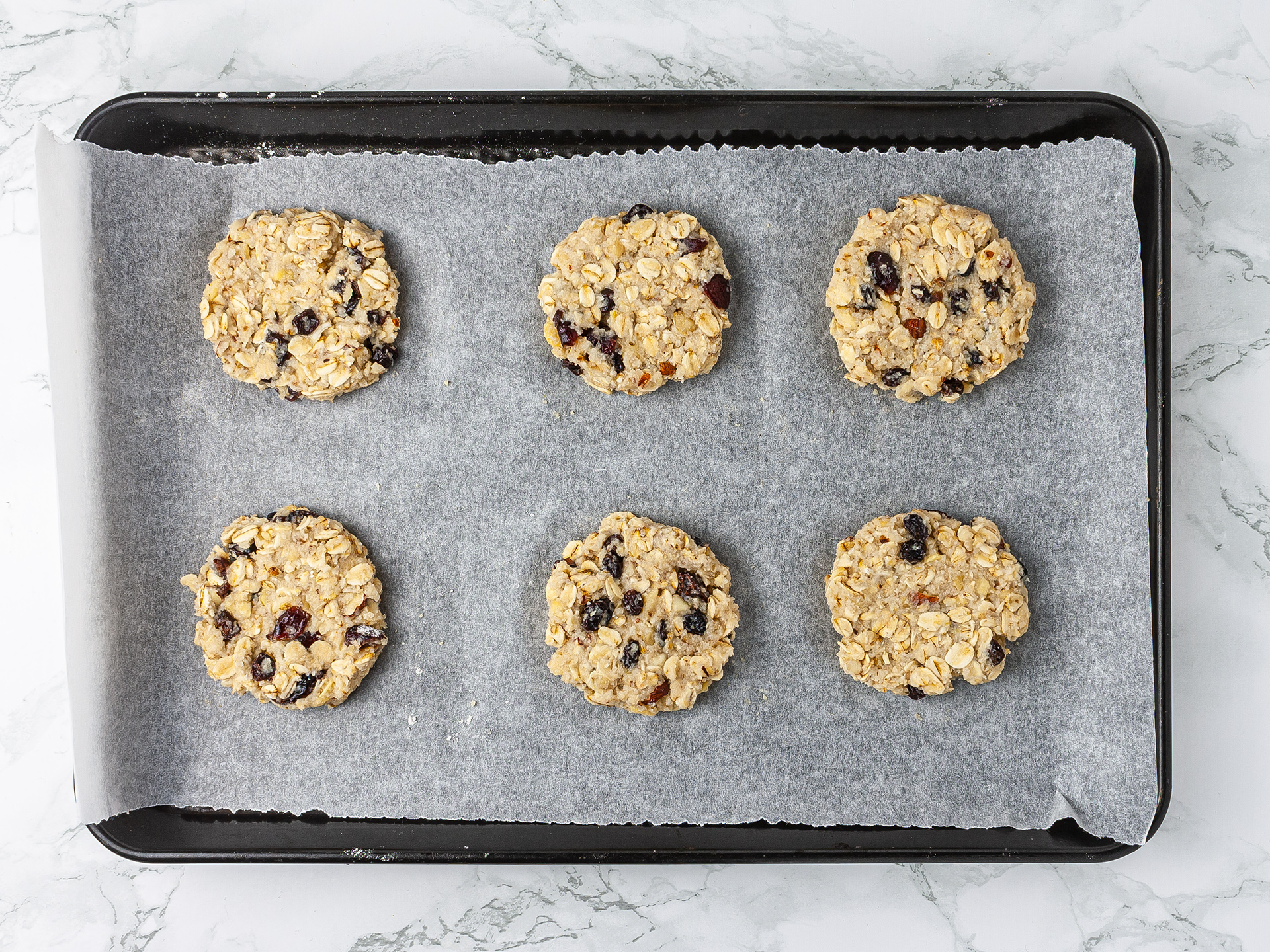 Raw vegan applesauce dough shaped into cookies on a tray