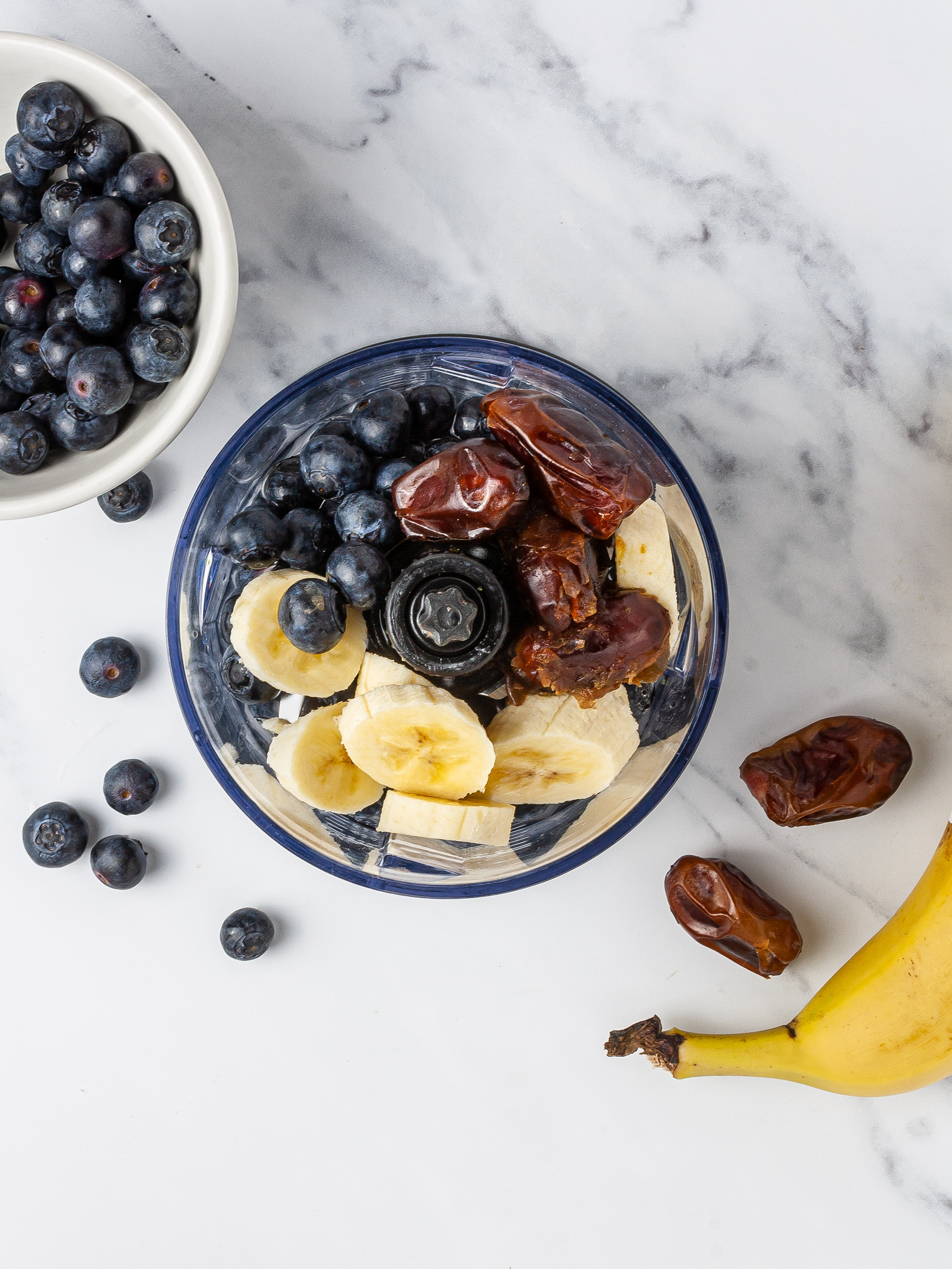 Bananas, dates, blueberries, and coconut water in a food processor for smoothie.