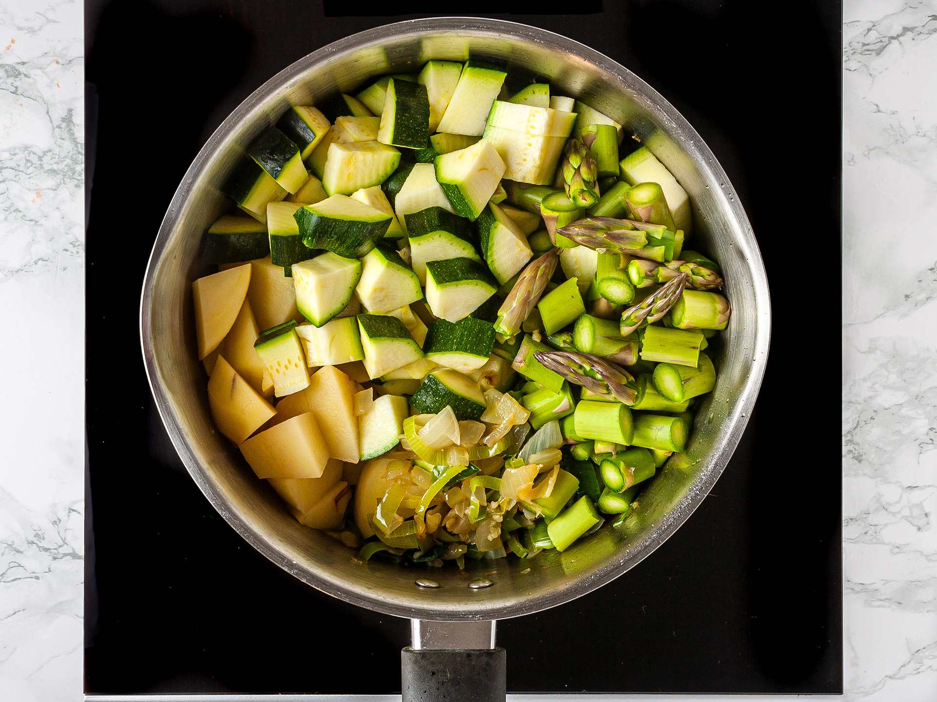 zucchini, potatoes, leeks, asparagus cooking in a pan