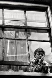 Amsterdamse jongen hangt uit een schuifraam