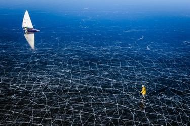 Schaatser en windzeiler op het ijs