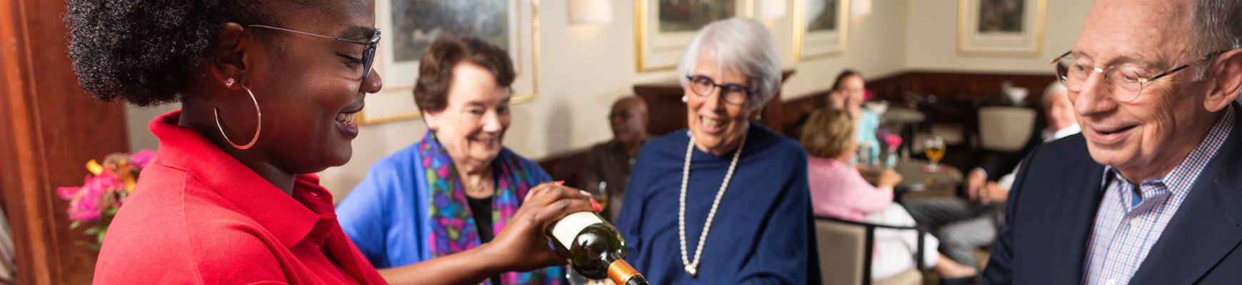 A server is pouring drinks for seniors during happy hour