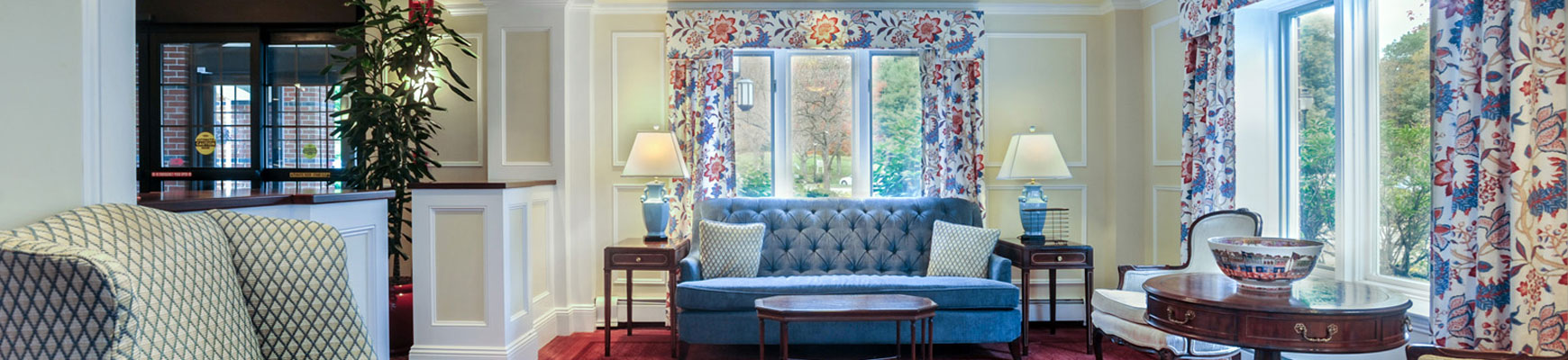 A floral and blue themed community room at Fox Hill Village senior living community in Massachusetts