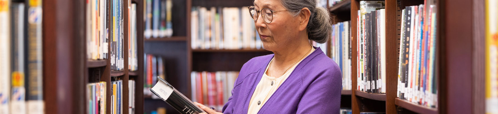 A senior woman looks at a book taken from the shelf in the community library