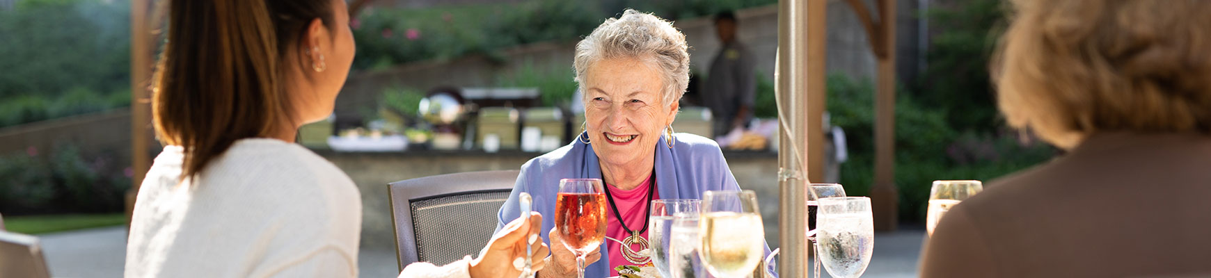 Seniors enjoy wine with their meal on the outdoor patio