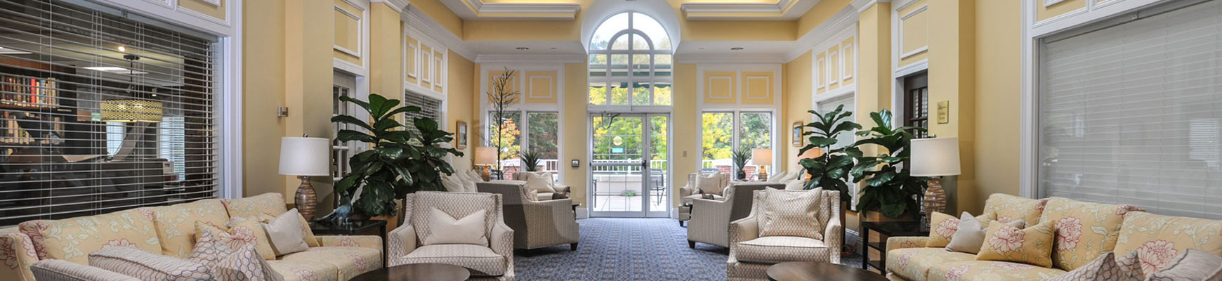 A yellow and floral themed community room at Fox Hill Village senior living community in Massachusetts