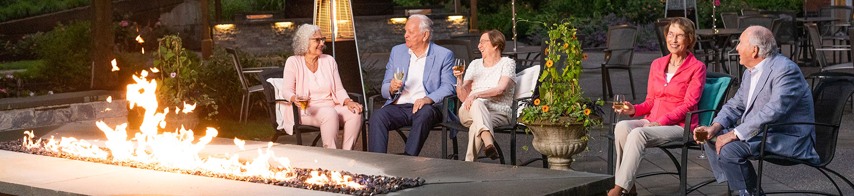 Seniors sitting outside on a patio close to a firepit enjoying an evening glass of wine