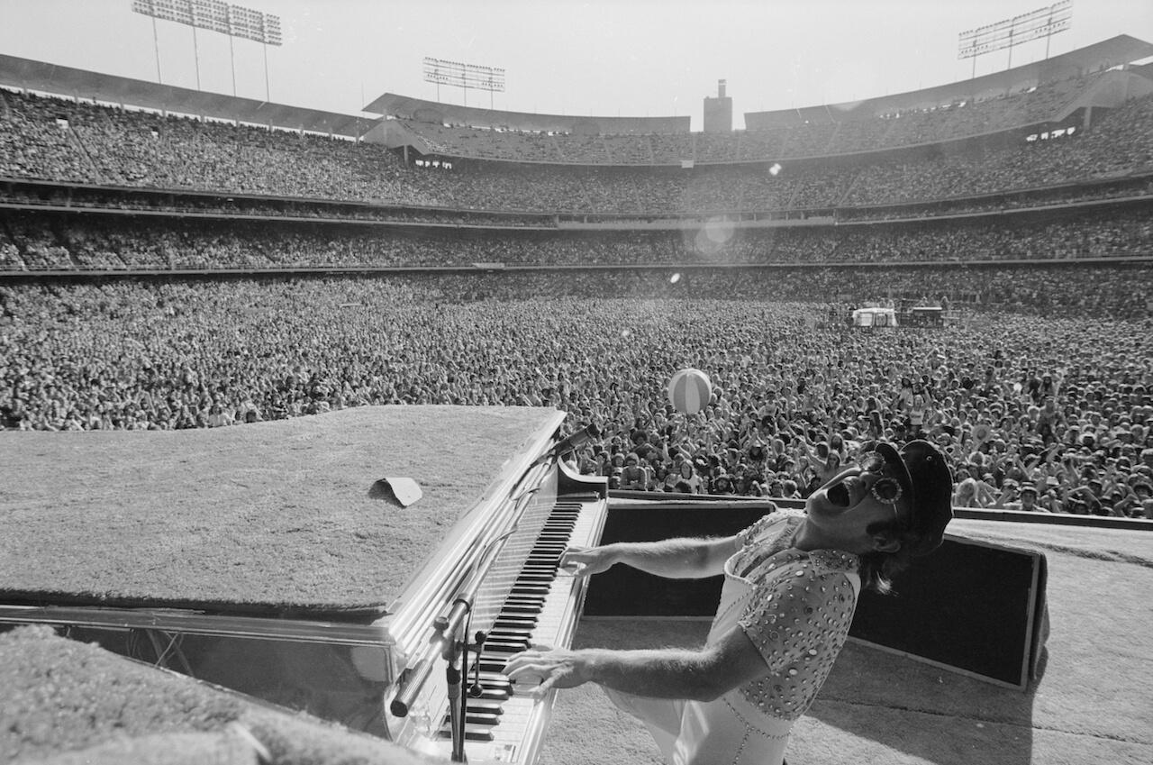 black and white photo of elton john performing on piano to arena
