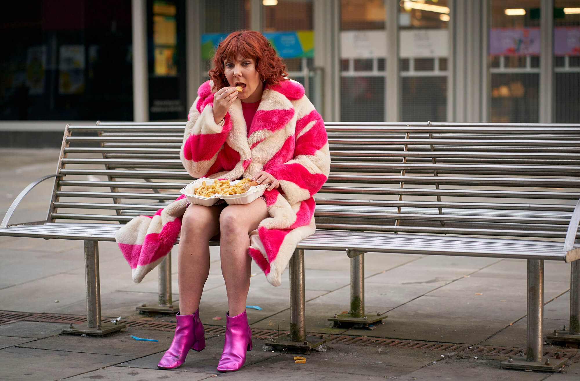 woman in pink eating on a bench