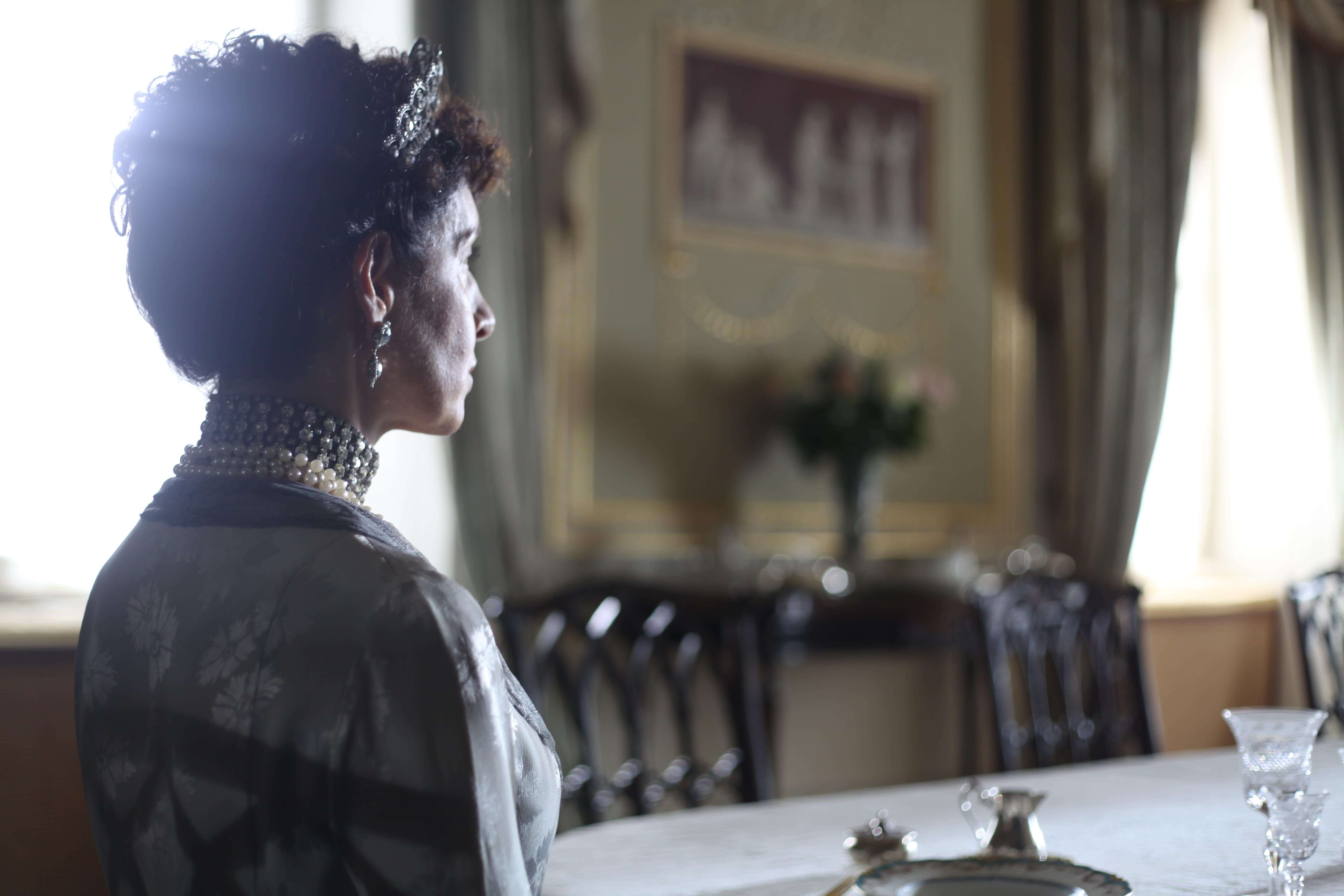 woman dressed as queen mary sat at table