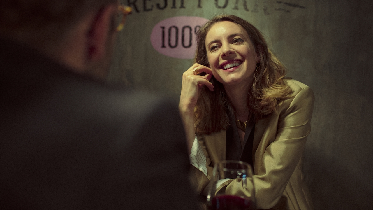 woman getting a drink in a bar and laughing