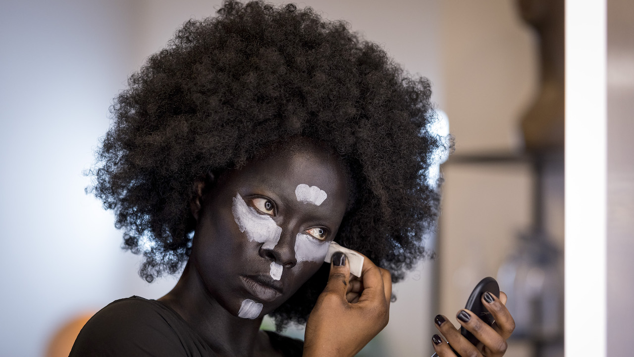 Woman putting on creative makeup for a chance to be Britain's next makuup star