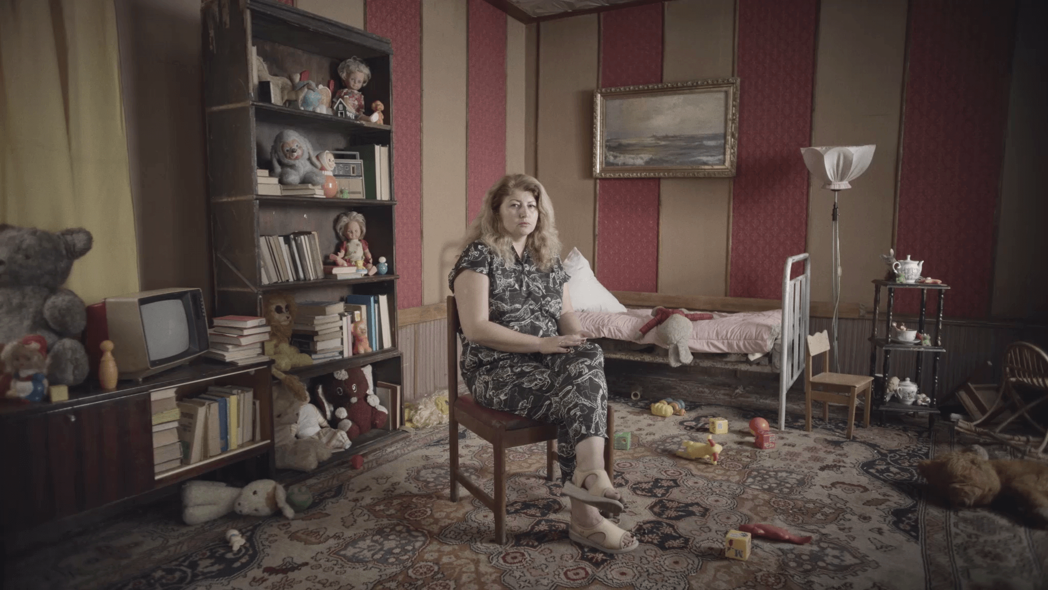 woman sat on chair in abandoned bedroom in chernobyl
