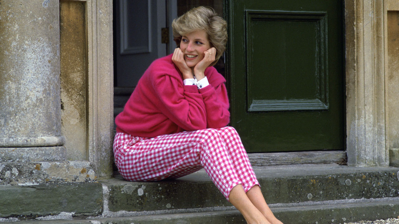 princess diana in pink outfit sat on stairs