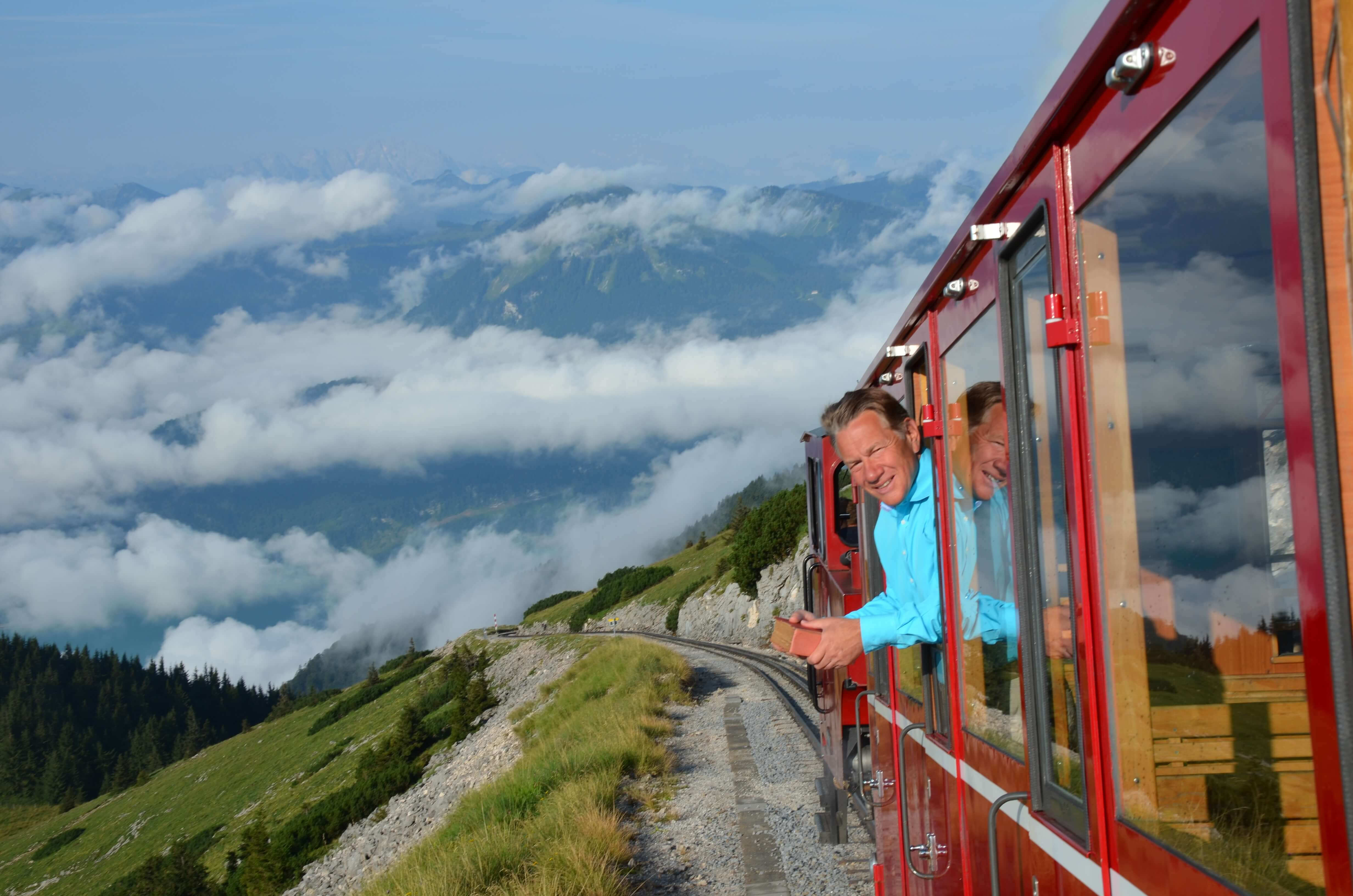 michael portillo leading out of train with mountains in background