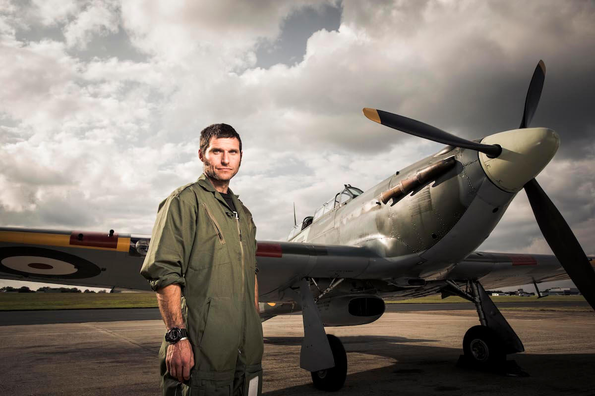guy martin standing in front of WWII fighter plane