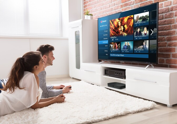 Young renting couple watching Freesat on TV