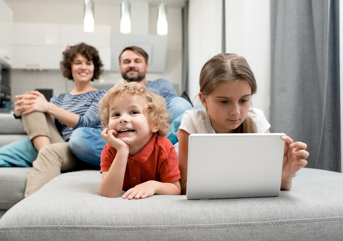 family watching Freesat and using tablet internet