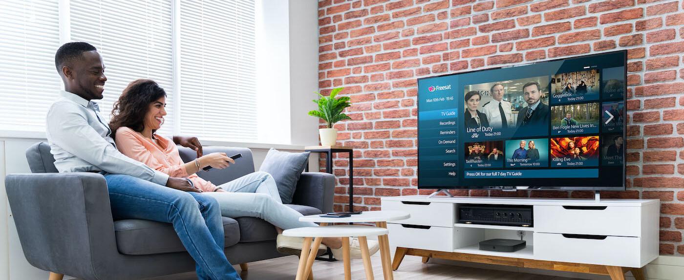 Couple sitting on sofa watching Freesat TV